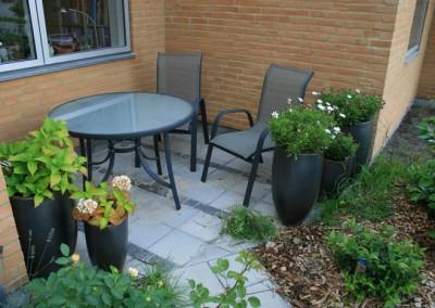 Lille terrasse udført i 25x25 cm fliser og striber m Chaussesten i blåsort