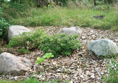 Haveanlæg Bødskov surbundsbed med store sten og flis til sidst ,passer fint ind i naturen omkring grunden ,flisen holder ukrudt nede og holder på fugten